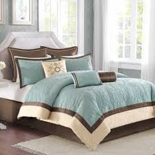 bedroom white curtains brown carpet grey simple bed bedding blue striped pillow wooden table lamp