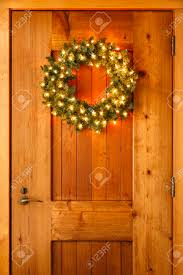 How To Hang Lighted Wreath On Door Beautiful Lighted Evergreen Wreath With Lights Hanging On Wooden