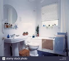 Runder Spiegel über Dem Sockel Becken In Weiß Gefliestes Badezimmer