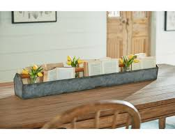 you will come up with lots of uses for this metal trough with wood handle so fill it with anything you want to and it will make a great eye catching piece