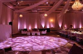bacara ballroom off white chiffon d with white seamless floor floor wash lighting and large crystal chandelier