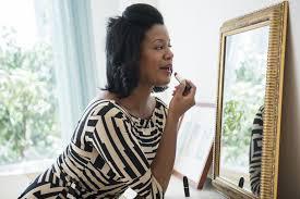 older woman applying makeup