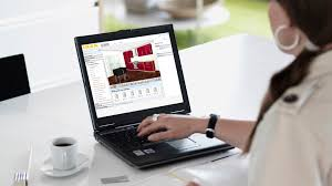 A Woman Sitting At A Table Having A Coffee And Using The IKEA Home Planner  3D. 3D Kitchen Planner