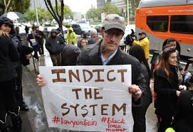 Protester With Indict The System Sign