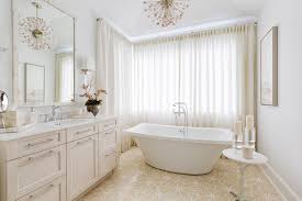 you can make a chandelier work in a smaller bathroom but choose a small fixture rather than a large one like the elegant chandelier seen here