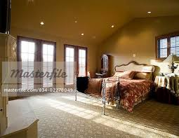 master bedroom with vaulted ceiling and window light spilling through double french doors stock photo