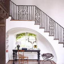 arched alcove under stairs filled with desk and chair alcove office