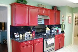 simple small metal gasstove between big red kitchen cabinets close green wall paint