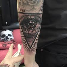 Black And Grey Crying Eye In Triangle Tattoo On Left Arm