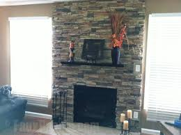 A beautiful fireplace surround built with faux stacked stone panels by a 50  year old woman