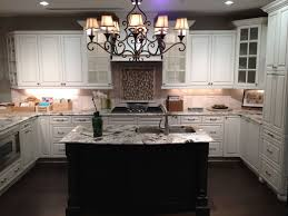 glamorous vintage feel kitchen design with marble countertop over classic chandelier and u shape white cabinet also under mount stainless steel sink plus