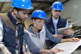 Industrial Engineers Meeting In Mechanical Factory Stock Photo