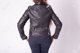 stock photo young woman in leather jacket rear view on back