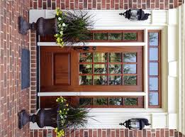 exterior brown wooden and glass entry doors connected by double glass windows with brown wooden