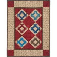 hole in the barn door quilt kit traditional hole in the barn door blocks in varied colors are set in a neutral background surrounded by a brown border