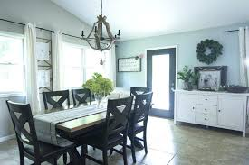 modern farmhouse dining room a modern farmhouse chandelier makes the space in this dining room modern