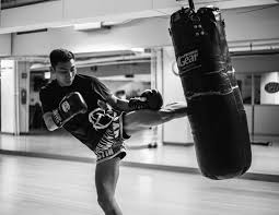 3840x2967 a man wearing boxing gloves kicking a punching bag at a gym in manhattanbag work 4k wallpaper and background 79826