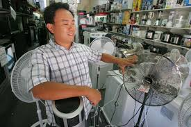 Alan Ly tries to cool himself in a electrical appliance shop in Collingwood  - ABC News (Australian Broadcasting Corporation)