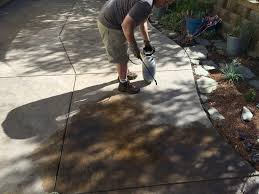 applying surecrete ecostain to a concrete patio with a pump up sprayer