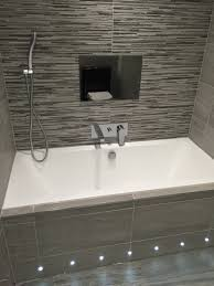 with a feature tiled on the walls and a darker stone effect tile on the floor giving a more natural feel finally the shower basin toilet mirror