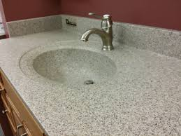 solid surface custom bathroom countertops in grey stone like color and a faucet on wooden counter