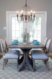 the dining room is illuminated with a dark metal chandelier and sed with bright fortable