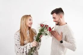 Encantadora mujer dando flores al hombre   Foto Gratis