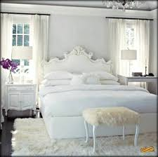 nightstand and table lamp with white headboard also bedding and fur bench with sheepskin throw rug