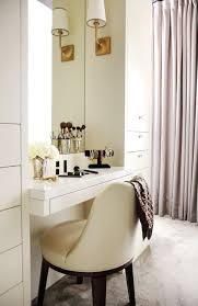 chic dressing room features a built in dressing table with drawer paired with an ivory leather vanity chair under inset mirror illuminated by brass sconces