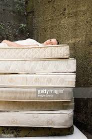 stack of mattresses. woman on pile of mattresses stack a