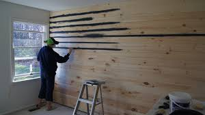 painting navy blue paint on tongue and groove boards installed on wall