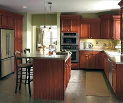 cherry cabinets dark kitchen by cabinetry with light quartz countertops