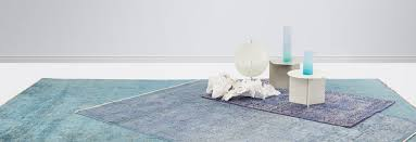 overdyed overlapping rugs in diffe sizes and shades of blue two small white geometric tables with
