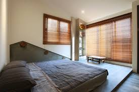 bedroom grey shabby bed sheet and brown horizontal wooden window blinds connected by beige wall