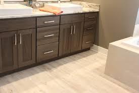 luxury vinyl plank flooring with dark shaker cabinets in bathroom