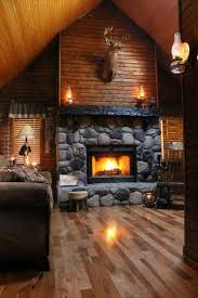 log cabin lighting ideas. aesthetic interior decor for log cabins with oil lamp style wall light and upholstered loveseat sofa also natural stone fireplace mantel under preserved cabin lighting ideas