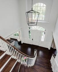 a stately lantern style light fixture hangs above the home s two story entry and