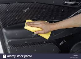 hand with microfiber cloth cleaning interior car door panel