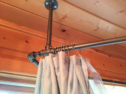 used black iron piping to create a shower curtain rod that surrounds our corner jetted tub