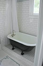 interior white plastic shower curtain and black bathtub with claw legs on white tile floor