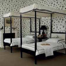 black and white furniture bedroom. Twin Black Four-poster Beds Against A Backdrop Of Floral Wallpaper And White Furniture Bedroom