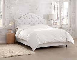 this elegant upholstered bed features diamond tufting on the