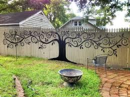 Gorgeous tree mural art on garden fence