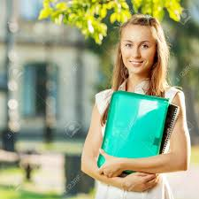 student w is standing the folder and copy book on the stock photo student w is standing the folder and copy book on the university campus background at the start of a school year in college