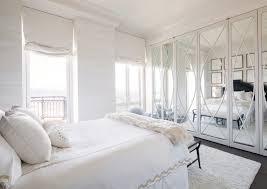 floor to ceiling mirrored french closet doors white walls and dark hardwood floors white rug white