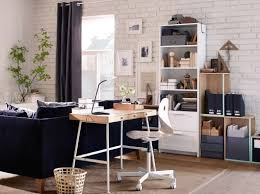 a home office inside the living room consisting of a desk in bamboo with white steel