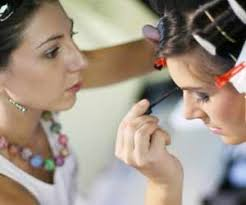 makeup artist working on model before photo shoot