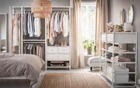 white furniture in bedroom. A Medium Sized Bedroom Furnished With Open Floor-to-ceiling Storage, Consisting Of White Furniture In