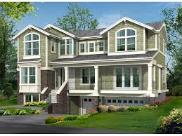 raised two story house design has uncommon style and drive under garage