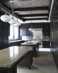large black kitchen with beam ceiling pendant lighting and 2 islands